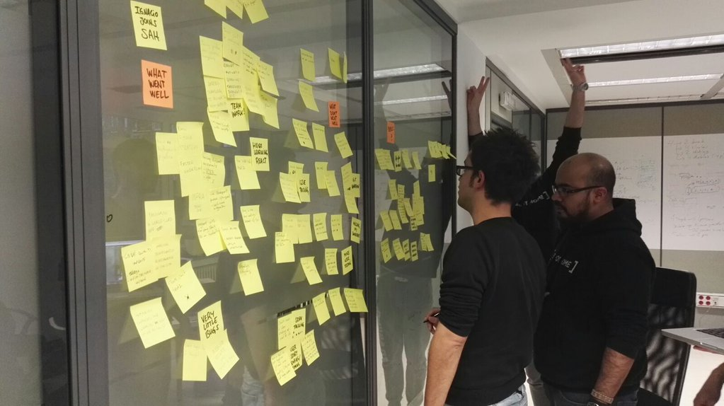 Two men looking at sticky notes on a wall